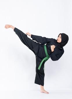 Les femmes hijab portant des uniformes de pencak silat avec des ceintures vertes effectuent des mouvements de haut