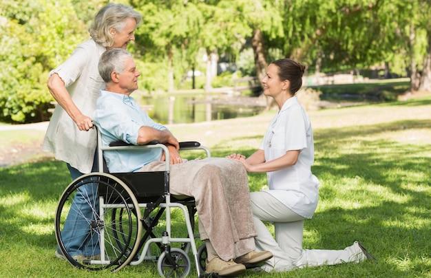 Femmes avec un homme d'âge mûr assis dans une chaise roulante au parc