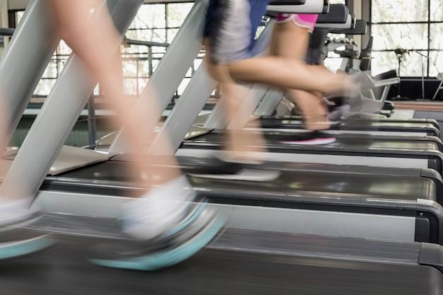 Femmes et hommes qui courent sur un tapis roulant au gymnase