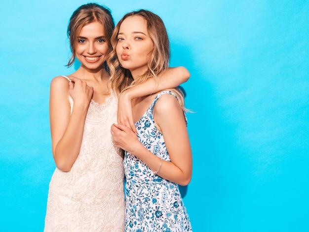 Femmes insouciantes sexy posant près du mur bleu. s'amuser et se faire des câlins.les modèles montrent une bonne relation.la femme fait face au canard