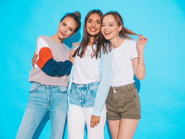 Femmes insouciantes sexy posant près du mur bleu en studio. modèles positifs s'amusant et étreignant