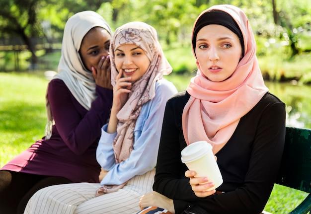 Femmes islamiques bavardant et intimidant leur ami