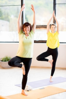 Les femmes jeunes et plus âgées portant des vêtements de sport font du yoga ensemble à l'intérieur à la maison ou dans une salle de sport
