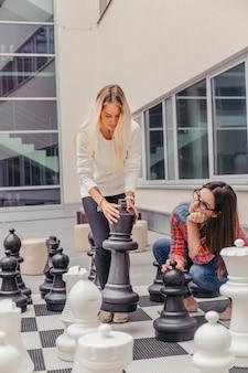 Femmes jouant aux échecs géants