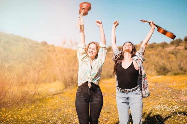 Femmes joyeuses avec ukulélés appréciant la météo