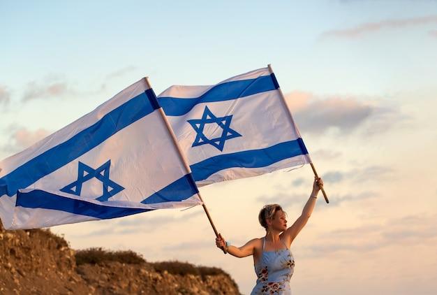Les femmes juives patriotes vêtues d'une robe bleue tiennent le drapeau d'israël dans ses mains au coucher du soleil à l'extérieur
