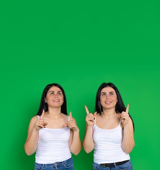 Femmes jumelles, dans les mêmes vêtements décontractés, pointant l'index vers le haut