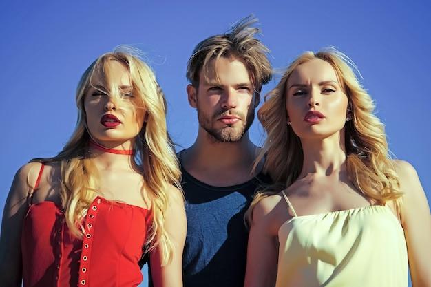 Femmes jumelles avec homme sexy sur fond de ciel bleu. triangle amoureux et romance.