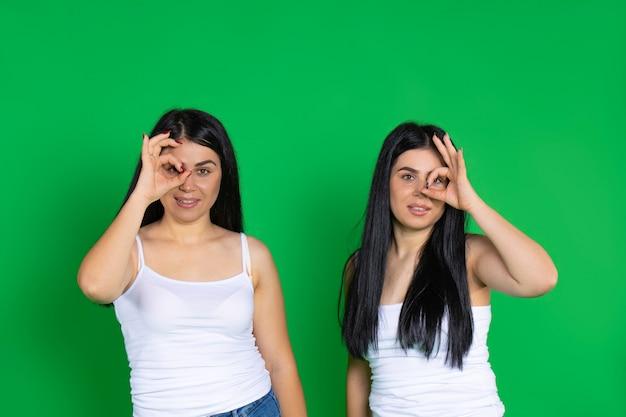 Les femmes jumelles montrent que tout va bien sourire mignon
