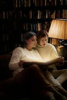 Femmes lisant d'un livre rougeoyant