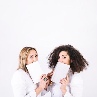 Femmes avec des livres en regardant la caméra