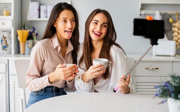 Femmes ludiques à la maison prenant des selfies