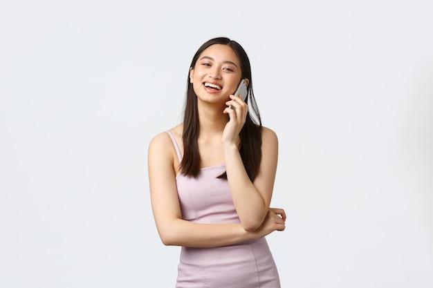 Femmes de luxe, concept de fête et de vacances. femme asiatique souriante insouciante en robe de soirée parlant au téléphone, riant heureux, ayant une conversation sur mobile, fond blanc