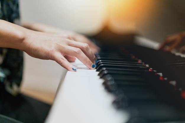 Femmes à la main sur le clavier classique gros plan de piano