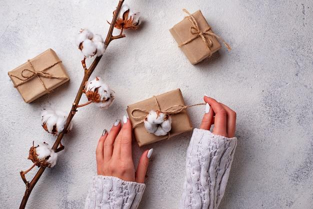 Femmes main emballer des boîtes à cadeaux en papier kraft.