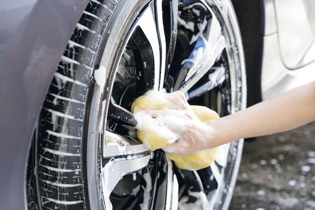Les femmes main avec une éponge en mousse lavage roue de voiture