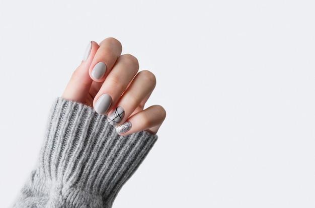 Les femmes à la main sur un pull gris avec manucure moderne se bouchent