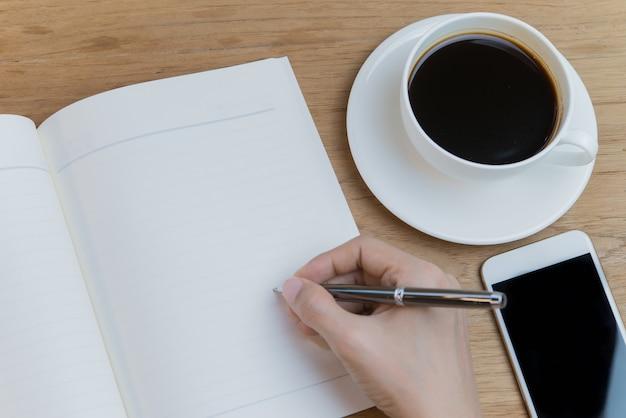 Femmes à la main qui écrit sur un livre vide avec café chaud et téléphone intelligent