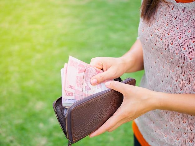 Femmes mains prenant de l'argent thai baht du portefeuille sur le terrain d'herbe verte.