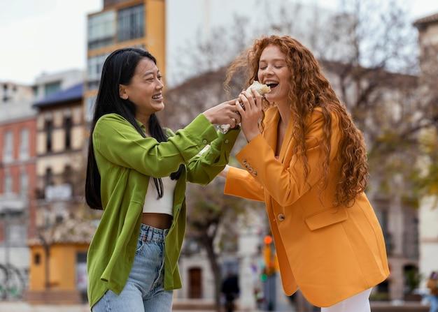 Les femmes mangeant de la nourriture de rue à l'extérieur