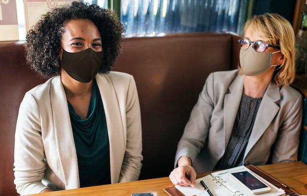 Femmes en masque facial au café pendant la pause déjeuner