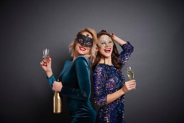 Femmes en masques buvant du champagne en studio shot