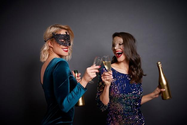 Les femmes en masques portant un toast à la bonne année