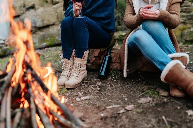 Des femmes méconnaissables tenant un verre de vin rouge dans un feu de camp se réchauffant à côté d'un feu.