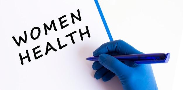 Les femmes médecins la main dans un gant médical fait une inscription dans un document
