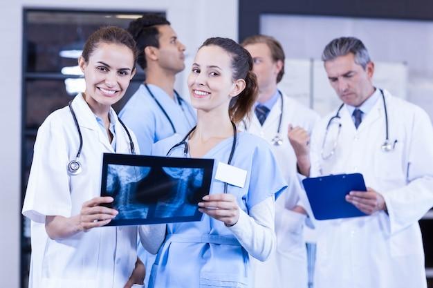 Femmes médecins vérifiant les rapports de rayons x et les médecins de sexe masculin discutant derrière
