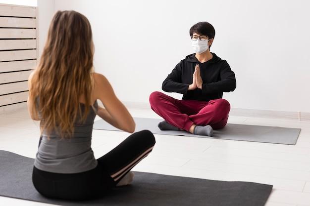 Femmes méditant avec un masque facial sur