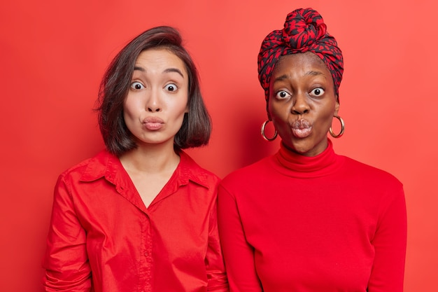 Les femmes les meilleures amies se tiennent étroitement les unes aux autres garder les lèvres arrondies attendre le baiser porte des vêtements rouges posent sur le mur lumineux du studio. modèles féminins de race mixte avec des lèvres plissées. expressions du visage