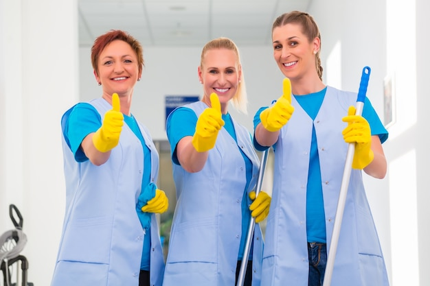 Femmes de ménage travaillant en équipe montrant le signe du pouce levé