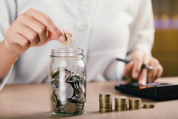Les femmes mettant la pièce dans la banque d'épargne de bouteille en verre et compte pour son argent tout en comptabilité financière