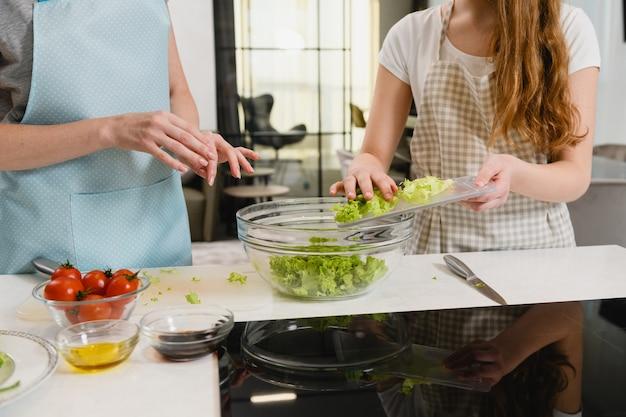 Les femmes mettent la salade verte au bol à l'intérieur