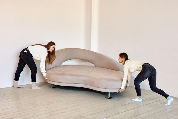 Les femmes minces déplacent un nouveau canapé à l'intérieur