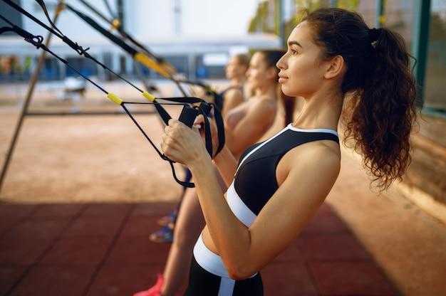 Femmes minces faisant de l'exercice avec des cordes sur un terrain de sport, entraînement de groupe en plein air