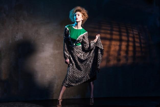 Femmes de mode dans la robe verte au-dessus de l'obscurité