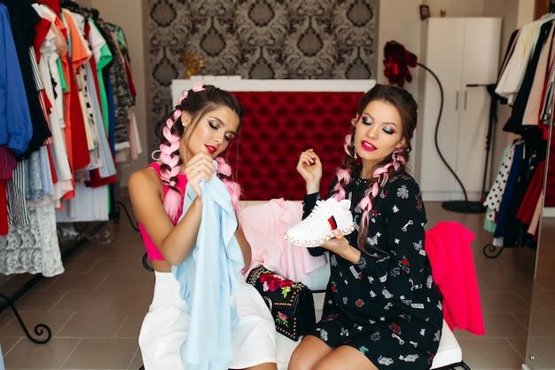 Femmes à la mode avec des tresses colorées et élégantes qui passent du temps en magasin.