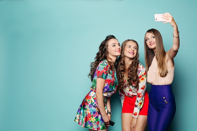 Femmes à la mode en vêtements faisant photo au téléphone intelligent.