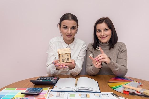 Femmes avec modèle de maison en bois et clé au bureau