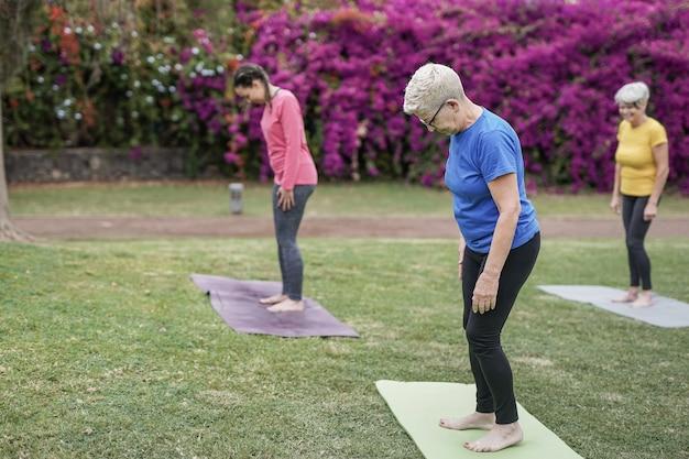 Femmes multi-générationnelles faisant du yoga au parc de la ville