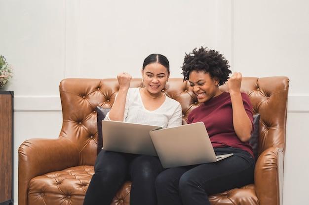 Femmes multiculturelles à l'aide d'un ordinateur portable sur un canapé se détendre sur le salon et rire de quelque chose à l'écran