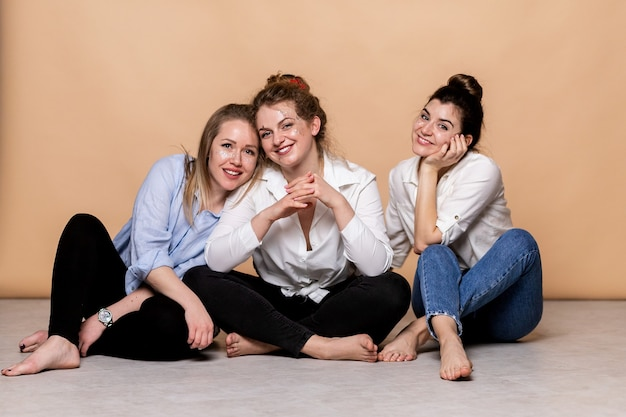 Femmes multiculturelles heureuses et en surpoids en soutien-gorge isolées sur beige. beauté diversifiée. trois dames multiethniques enveloppées dans des serviettes de bain posant souriant à la caméra sur fond beige. prise de vue en studio