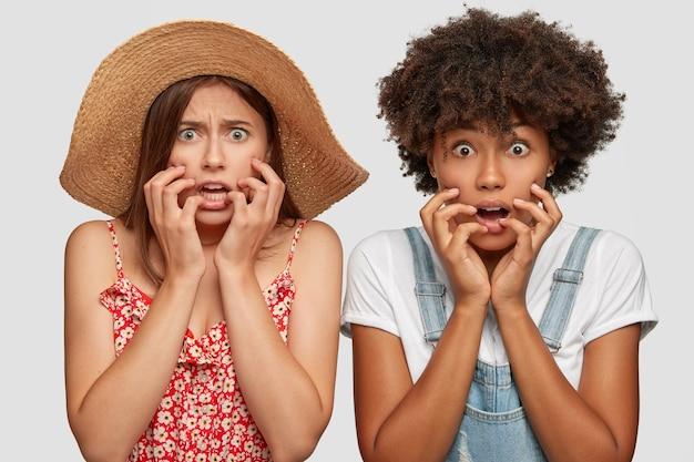 Les femmes multiethniques émotives effrayées regardent la caméra avec perplexité