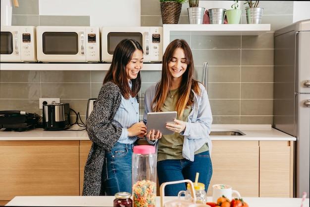 Femmes multiethniques gaies avec tablette dans la cuisine