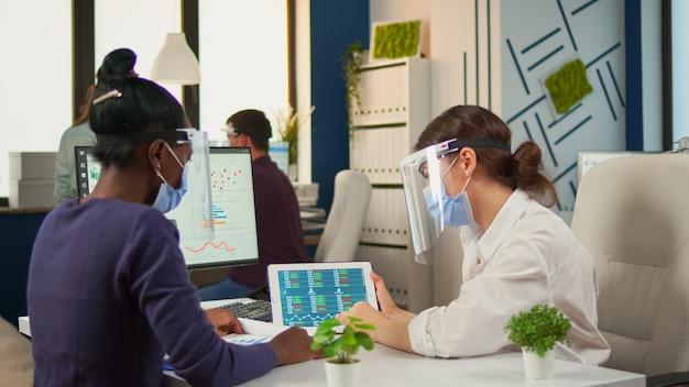 Femmes multiethniques avec masques de protection analysant les rapports annuels divers groupes d'hommes d'affaires travaillant et communiquant ensemble dans un bureau créatif avec une nouvelle norme, respectant la distance sociale.