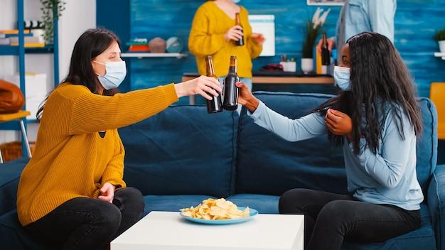 Femmes multiethniques avec des masques de protection tintant des bouteilles de bière assises sur un canapé enlevant un masque de protection buvant à une nouvelle fête normale