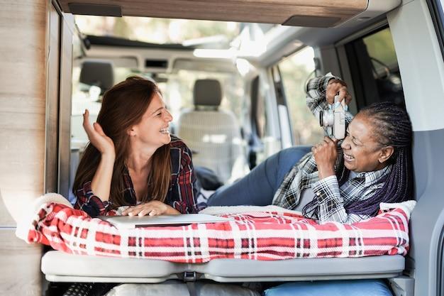 Femmes multiraciales matures s'amusant à l'intérieur d'un mini-van camping-car. femme âgée africaine prenant une photo avec un appareil photo vintage à son ami caucasien