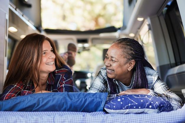 Des femmes multiraciales matures se détendent à l'intérieur d'un mini-van de camping lors de vacances sur la route dans la nature